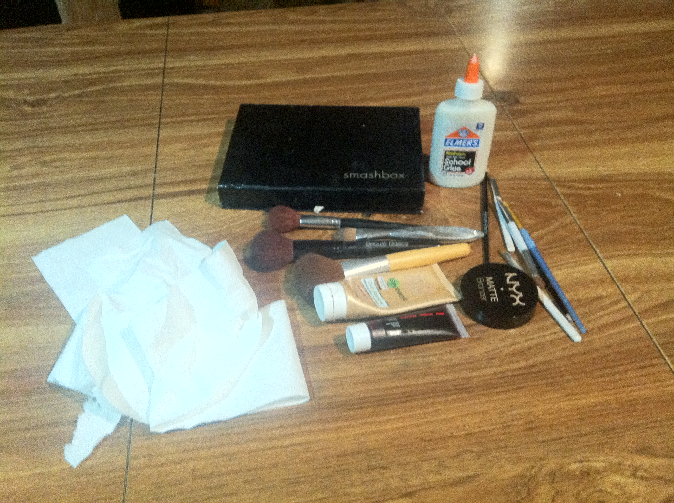 Many flesh colored makeup, eye shadows, toilet paper, fake blood, elmers glue, and makeup brushes.